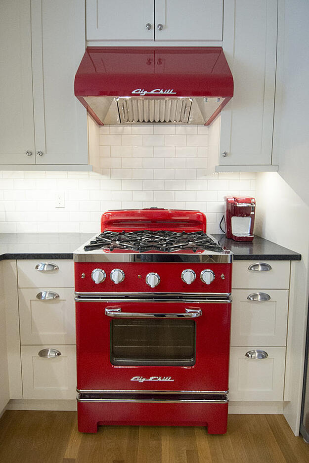 Photo of kitchen remodel with red big chill cooking range and hood