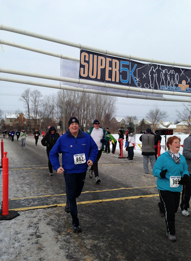 Doug Selby Crossing The Finish Line IN a 5K Race