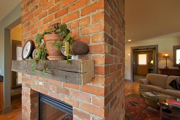 brick fireplace with wooden mantle.