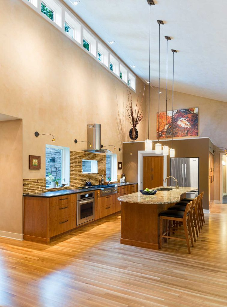 Open layout kitchen with high ceilings and no upper cabinets for accessibility and aging in place